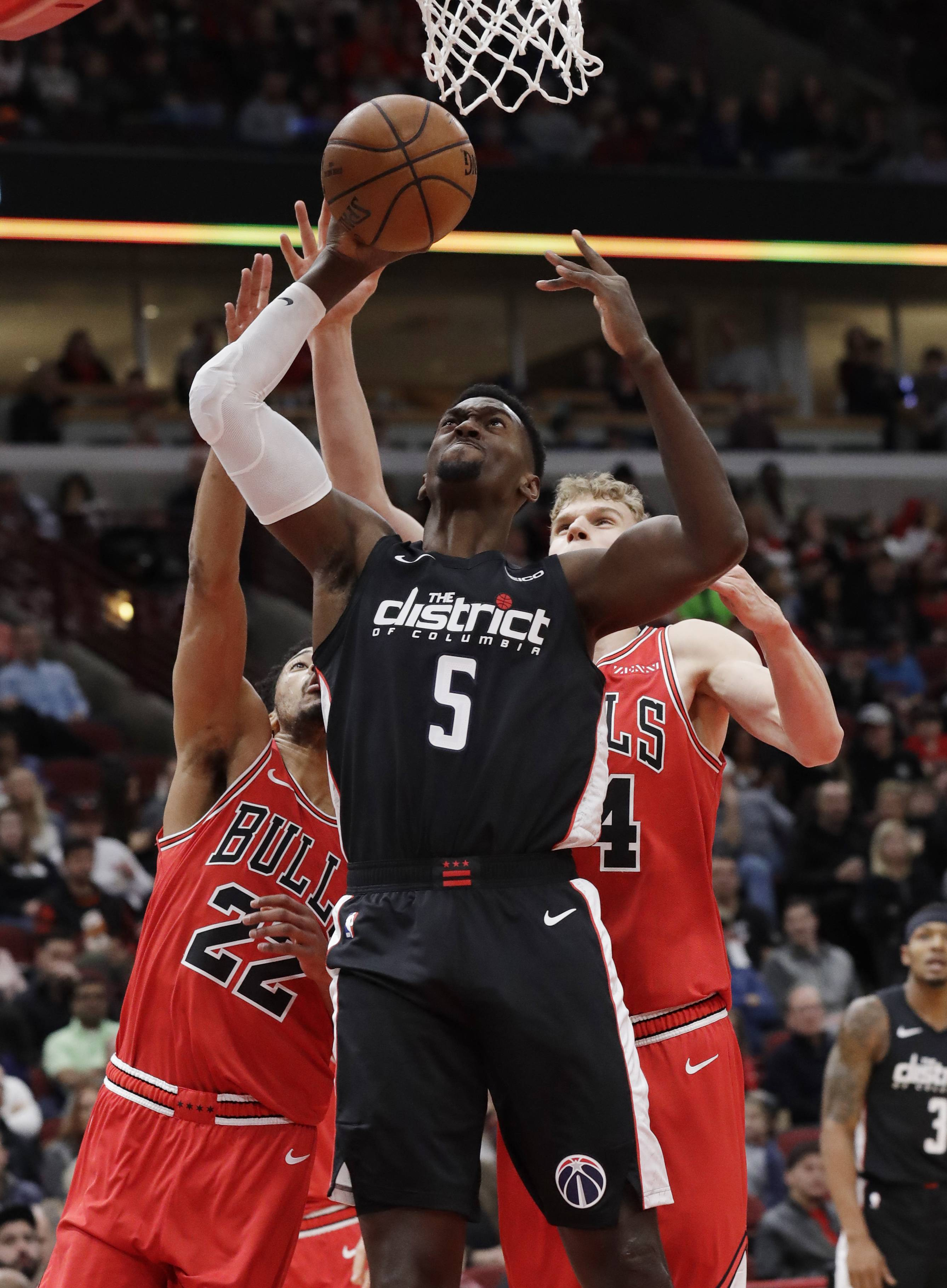 Washington Wizards forward Bobby Portis (5) goes up to shoot against Chicago Bulls forward Otto Porter Jr., left, and forward Lauri Markkanen during the first half of an NBA basketball game Saturday, Feb. 9, 2019, in Chicago.