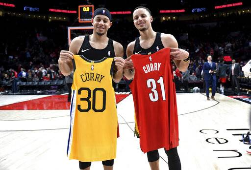 FILE - In this Dec. 29, 2018, file photo, Portland Trail Blazers guard Seth Curry, left, and his brother, Golden State Warriors guard Stephen Curry, exchange jerseys after an NBA basketball game in Portland, Ore. The Curry brothers are returning to their hometown of Charlotte, N.C, for the NBA All-Star weekend. Stephen, a two-time league MVP, will join younger brother Seth in the 3-point shootout on Saturday night at the Spectrum Center and then play in his sixth straight All-Star game on Sunday.