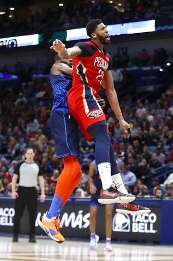 New Orleans Pelicans forward Anthony Davis (23) collides with Oklahoma City Thunder forward Nerlens Noel (3) after attempting to block a shot at the end of the first half of an NBA basketball game in New Orleans, Thursday, Feb. 14, 2019. Davis kept his left arm still as he walked to the locker room shortly after fouling Noel on an attempted shot block with his left hand. When the second half began, the Pelicans announced that Davis was out of the remainder of the game with a left shoulder injury, The Pelicans won 131-122.