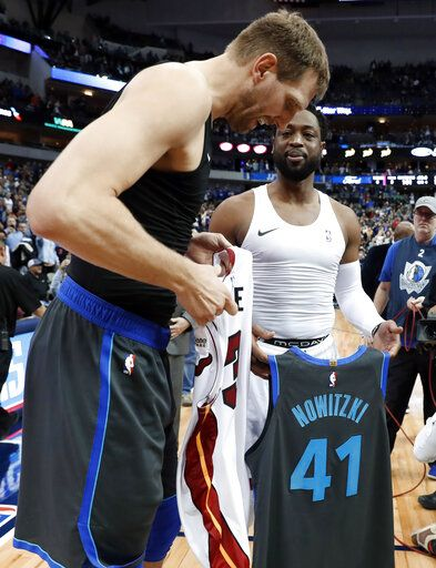 Dallas Mavericks' Dirk Nowitzki left, and Miami Heat's Dwyane Wade, second from right, talk as they swap jerseys after an NBA basketball game in Dallas, Wednesday, Feb. 13, 2019.