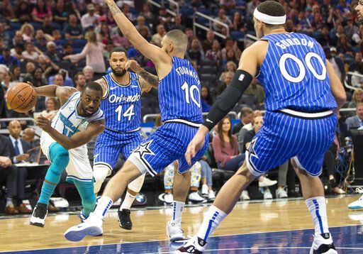 Charlotte Hornets guard Kemba Walker (15) dribbles against Orlando Magic guard D.J. Augustin (14), guard Evan Fournier (10) and forward Aaron Gordon (00) during the first half of an NBA basketball game in Orlando, Fla., Thursday, Feb. 14, 2019.