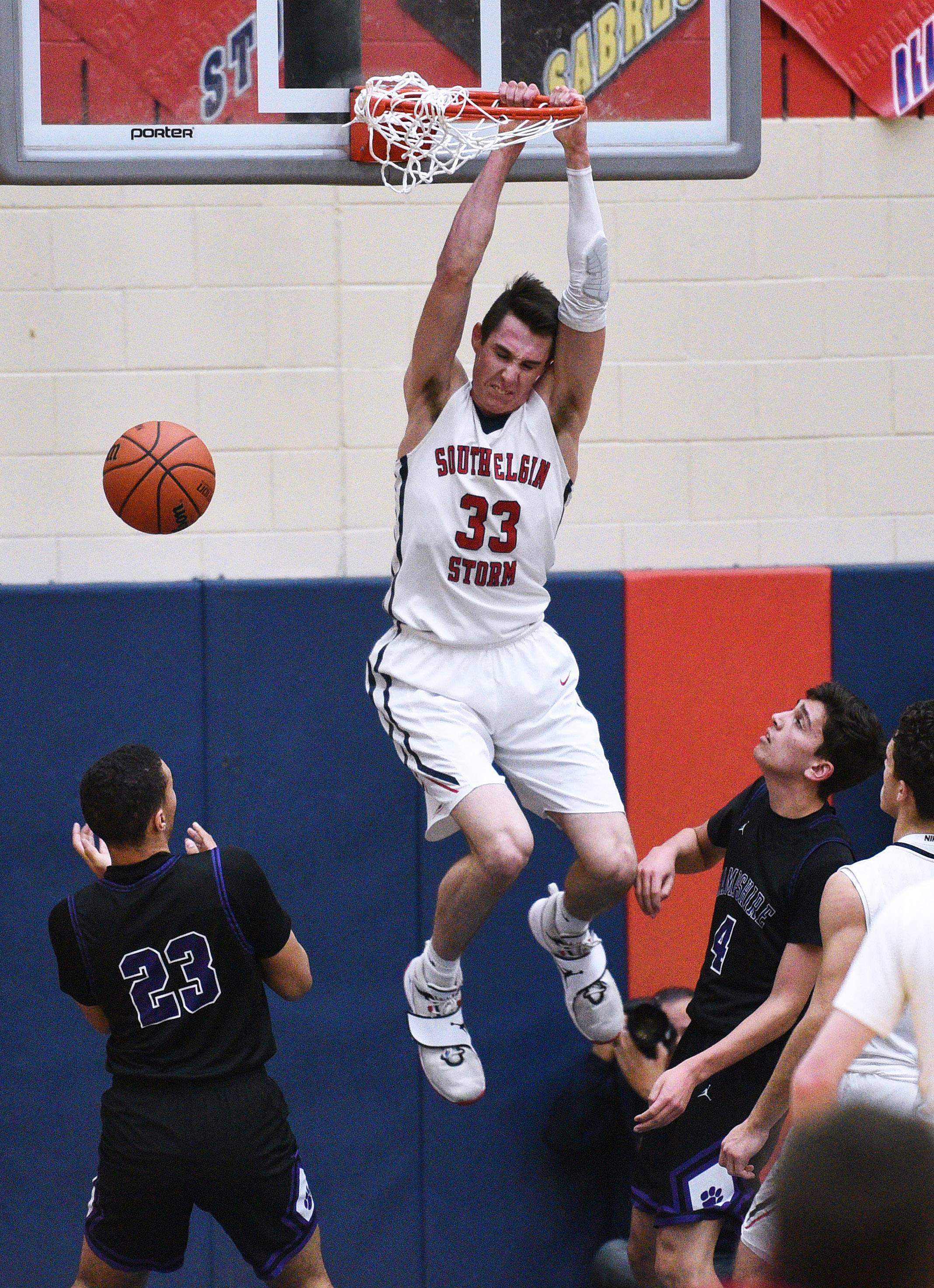 South Elgin's Vincent Miszkiewicz (33) hangs on the rim after a dunk as Hampshire's AJ Bishop (23) and Kyle Johnson (4) look on during Wednesday's Class 4A regional semifinal boys basketball game in South Elgin.