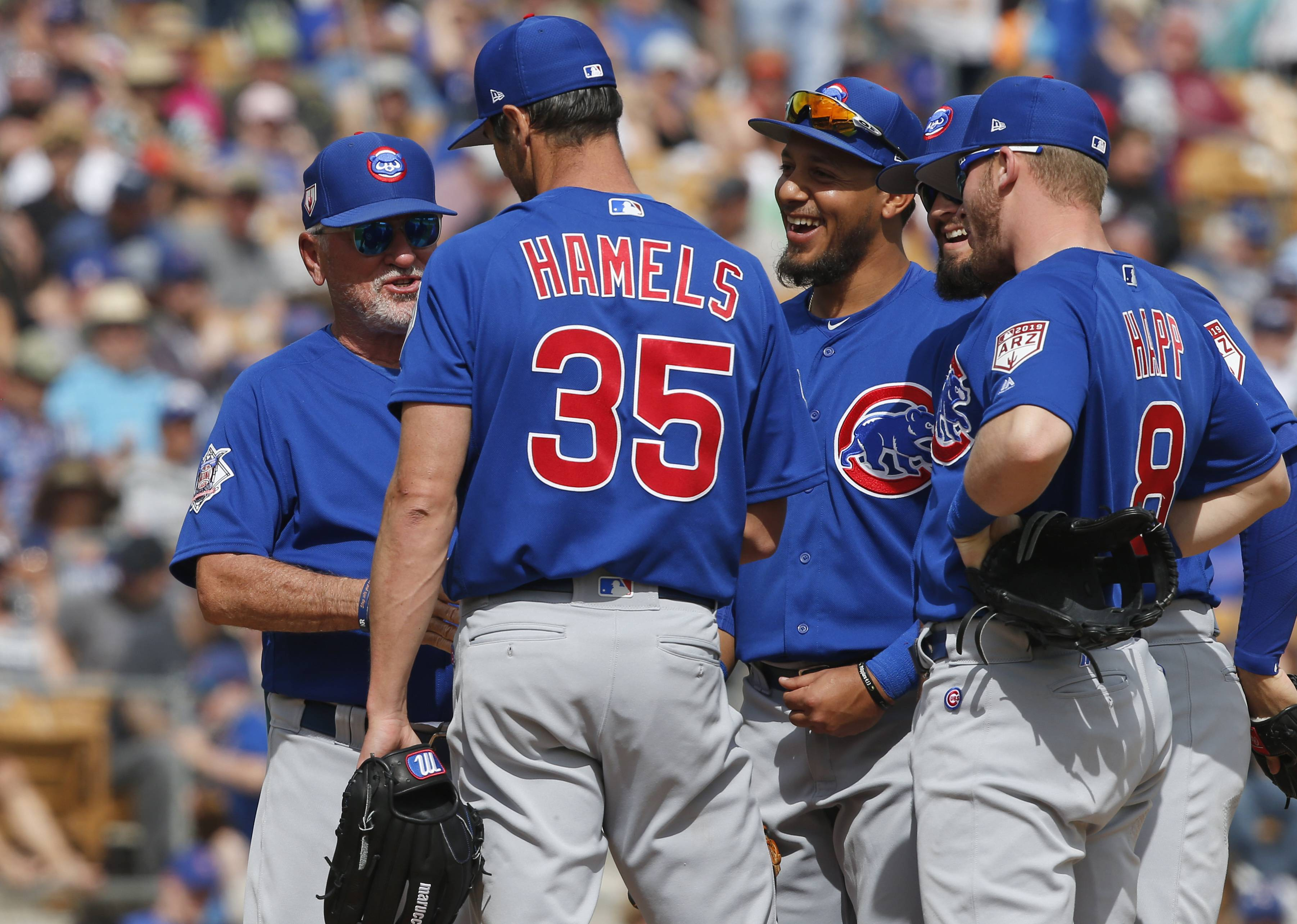 Chicago Cubs manager Joe Maddon, left, comes out to the mound to take starting pitcher Cole Hamels (35) out of the game as infielders, from left, Cristhian Adames, David Bote and Ian Happ wait during the fourth inning of a spring training baseball game Friday, March 15, 2019, in Glendale, Ariz. (AP Photo/Sue Ogrocki)