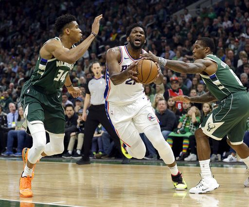 Philadelphia 76ers' Joel Embiid drives between Milwaukee Bucks' Giannis Antetokounmpo (34) and Eric Bledsoe (6) during the first half of an NBA basketball game Sunday, March 17, 2019, in Milwaukee.