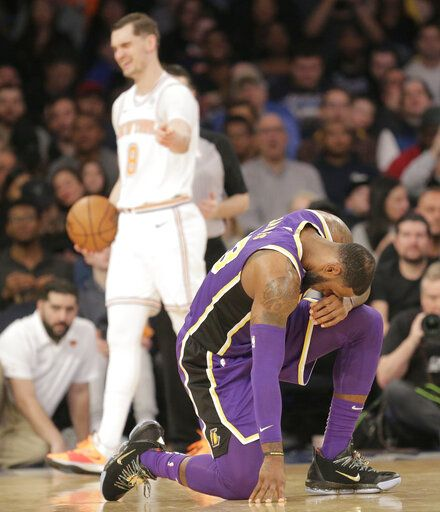 Los Angeles Lakers' LeBron James, right, and New York Knicks' Mario Hezonja react after Hezonja fouled him during the second half of an NBA basketball game, Sunday, March 17, 2019, in New York.