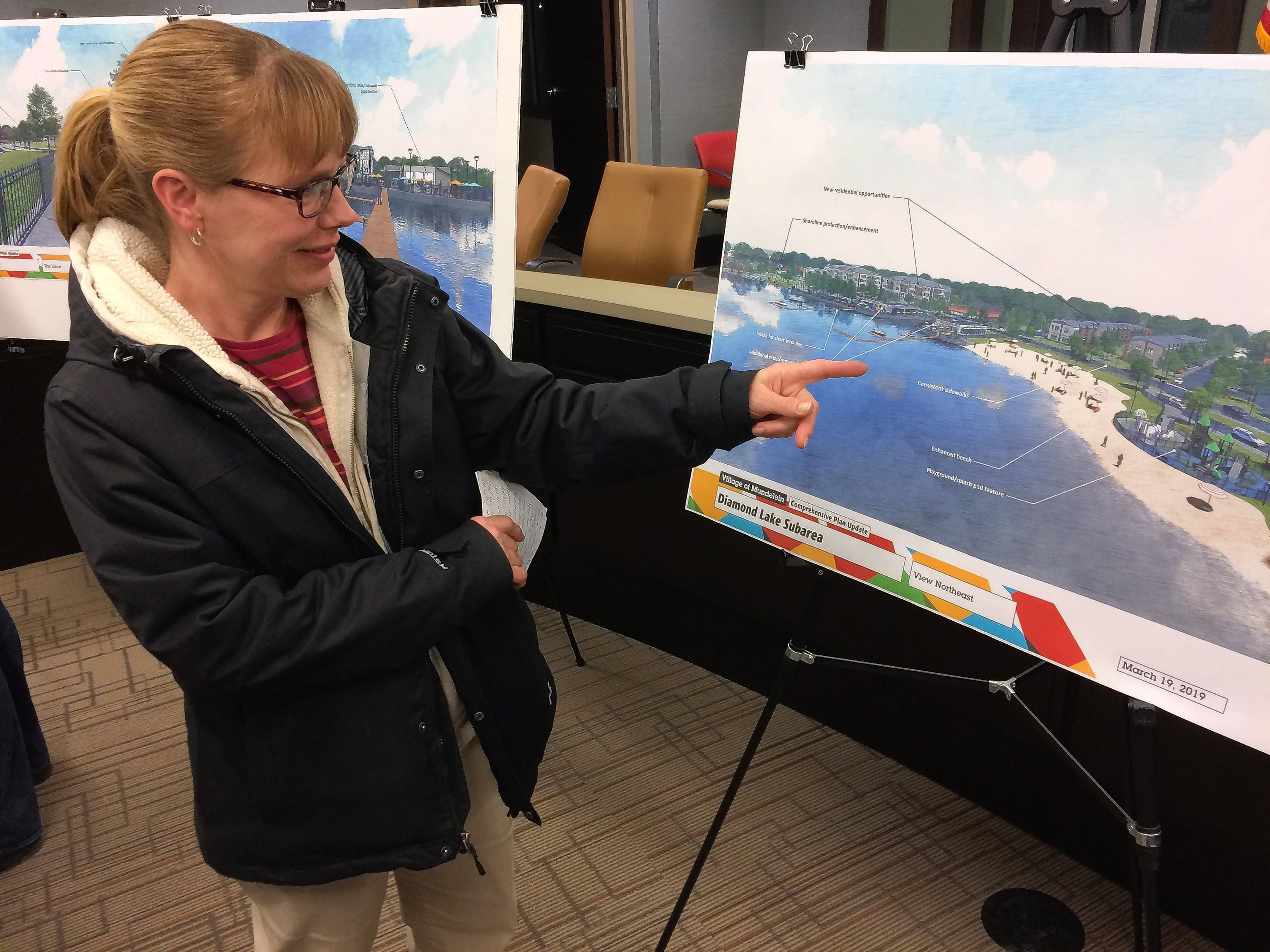 Mundelein resident Kristin May checks out one of the architectural designs for Diamond Lake on Tuesday during an open house at village hall.