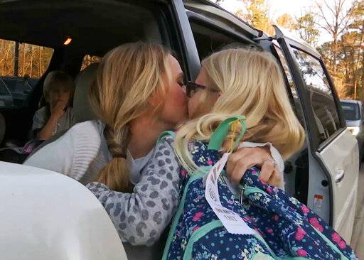 In this Wednesday, March 27, 2019, frame from video, Kacey Ruegsegger Johnson kisses her daughter, Logan, as she drops her off at her school in Cary, N.C. Dropping her kids off at school used to be the hardest part of Ruegsegger Johnson's day. She would cry most mornings as they left the car, and relied on texted photos from their teachers to make it through the day.