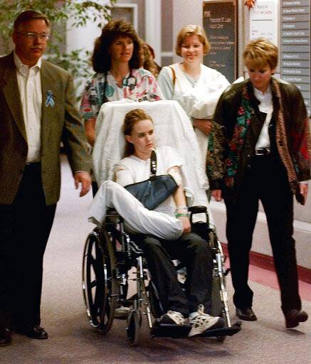 FILE - In this May 1, 1999, file photo, Kacey Ruegsegger, 17, is wheeled from a Denver hospital by Patty Anderson, center, after being released. Walking beside her are her parents Greg, left, and Darcy, right. Ruegsegger Johnson survived a shotgun blast during the 1999 shootings at Colorado's Columbine High School that left 12 students, one teacher, and both gunmen dead.