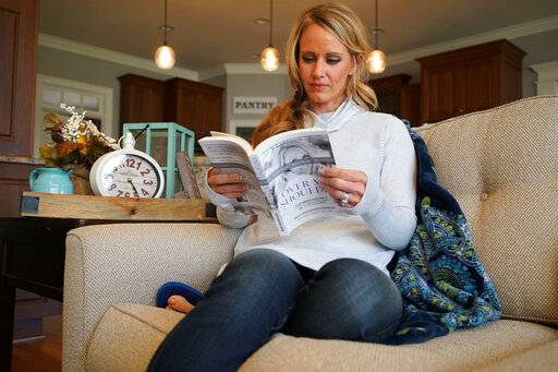 "In this Wednesday, March 27, 2019, photo, Kacey Ruegsegger Johnson pages through a copy of her memoir at her home in Cary, N.C. The book, ""Over My Shoulder,� recounts her physical, emotional and spiritual recovery following the 1999 massacre of Colorado's Columbine High School."