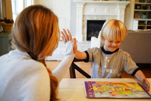 "In this Wednesday, March 27, 2019, photo, Kacey Ruegsegger Johnson high-fives with her son Corban as they finish a puzzle in their Cary, N.C., home. Twenty years after teenage gunmen attacked Columbine High School, Ruegsegger Johnson and other alumni of the Littleton, Colo., school have become parents. ""I'm grateful I have the chance to be a mom. I know some of my classmates weren't given that opportunity,� Ruegsegger Johnson said, tears springing to her eyes."