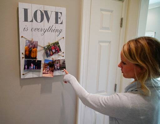 In this Wednesday, March 27, 2019, photo, Kacey Ruegsegger Johnson looks at photos of her family at her home in Cary, N.C. Ruegsegger Johnson survived a shotgun blast during the 1999 shootings at Colorado's Columbine High School that left 12 students, one teacher, and both gunmen dead.