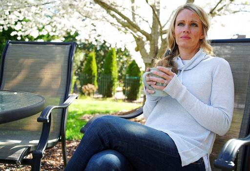 In this Wednesday, March 27, 2019, photo, Kacey Ruegsegger Johnson enjoys a coffee in a light spring breeze in the back yard of her home in Cary, N.C. For the last 20 years since she was injured in the Columbine High School attack, she has lived with post-traumatic stress disorder, along with physical pain.  Now a mother of four, she has worked hard not to pass that fear on to her children.