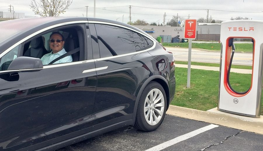 Tesla owner Sanjiv Akhand of Naperville charges his car in Rolling Meadows. He is dubious about bills pending in Springfield to hike vehicle registration rates for electric cars.