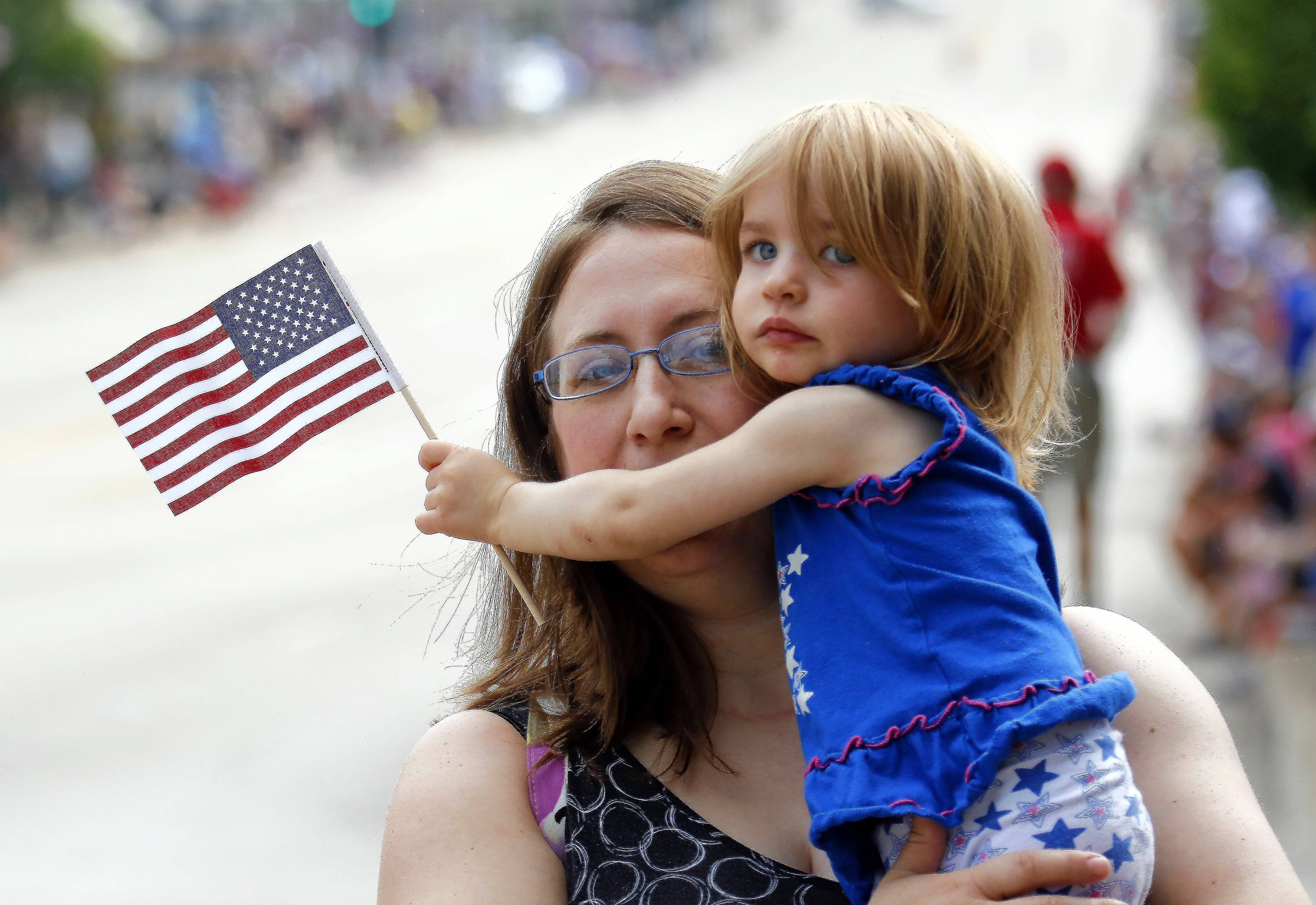 Julia Fredres of Elburn holds on tight to her daughter Abby during last year's Memorial Day parade in St. Charles. This year's parade steps off at 10 a.m. Monday, May 27.