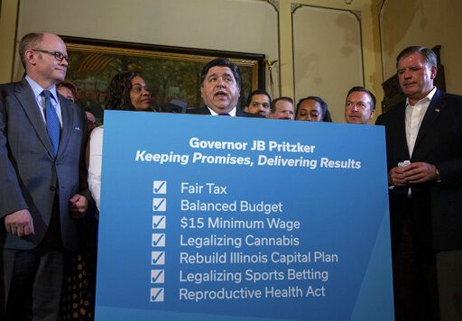 Illinois Governor J.B. Pritzker holds a press conference surrounded by both Republicans and Democrats from the legislature touting the accomplishments of the Spring Session after the Illinois Senate approved funding for the capital construction plan, legalized sports betting and gambling expansion, Sunday, June 2, 2019, in Springfield, Ill. (Justin L. Fowler/The State Journal-Register via AP)