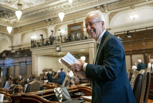 Illinois Sen. Terry Link, D-Vernon Hills, holds up the gaming expansion bill he sponsored as it awaits a vote in the Illinois Senate during overtime of the Spring Session at the Illinois State Capitol, Sunday, June 2, 2019, in Springfield, Ill. The Illinois Senate approved funding for the capital construction plan, legalized sports betting and gambling expansion. (Justin L. Fowler/The State Journal-Register via AP)