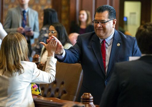Illinois State Sen. Martin Sandoval, D-Chicago, gets a high five from Illinois State Sen. Melinda Bush, D-Greyslake, after the passing of a capital construction plan on the floor of the Illinois Senate during overtime of the Spring Session at the Illinois State Capitol, Sunday, June 2, 2019, in Springfield, Ill. The Illinois Senate approved funding for the capital construction plan, legalized sports betting and gambling expansion. (Justin L. Fowler/The State Journal-Register via AP)