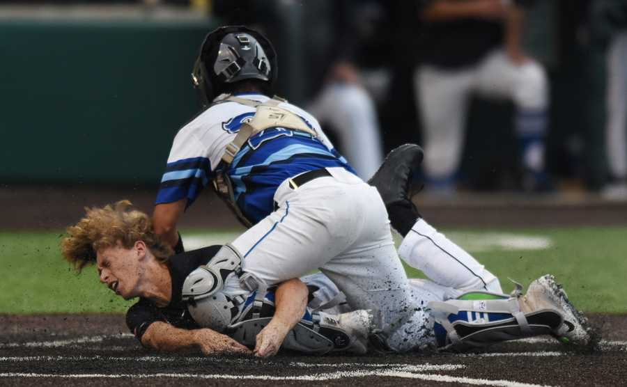 Edwardsville's Aaron Young scores the go-ahead run in the eighth inning under the tag by St. Charles North catcher Marco Torres during the Class 4A state baseball championship game in Joliet Saturday. Edwardsville won the game 3-2.