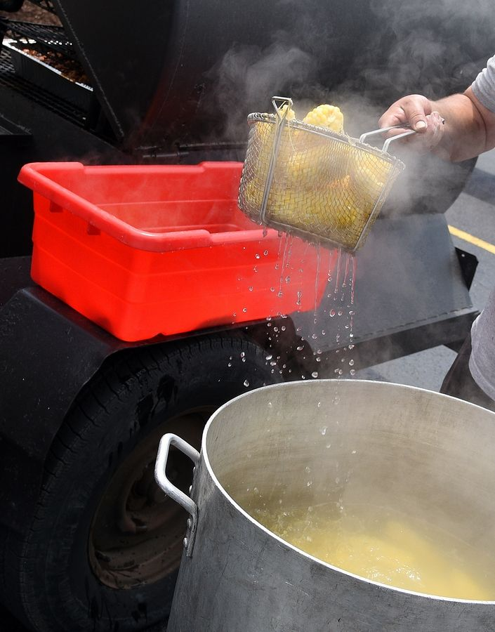 Rick West/rwest@dailyherald.comGale Martin of BBQ On Wheels pulls out some freshly boiled corn for a birthday celebration at JR Carlson Labs in Arlington Heights Tuesday.