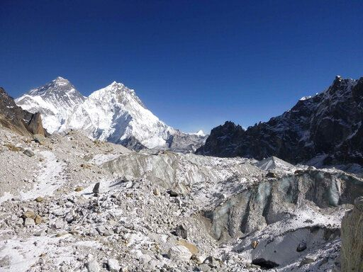 This 2014 photo provided by Joshua Maurer shows the Changri Nup Glacier in Nepal, much of it covered by rocky debris. The peak of Mt. Everest is partially obscured at background left. From 2000-2016, the Himalayan mountain range has been losing about 8.3 billion tons (7.5 billion metric tons) of ice a year, compared 4.3 billion tons (3.9 billion metric tons) a year between 1975 and 2000, according to a study published in the journal Science Advances on Wednesday, June 19, 2019. (Joshua Maurer via AP)