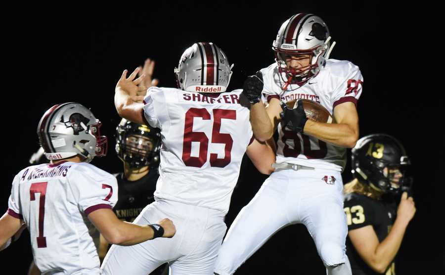 Dino Kaliakmanis, right, celebrates his second-quarter touchdown with teammates Robert Meyer-Shaffer, middle, and his brother, quarterback Athan Kaliakmanis.