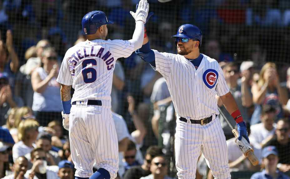 The Cubs' Nicholas Castellanos (6) celebrates with teammate Kyle Schwarber, right, after scoring on a Kris Bryant single during the second inning. The Chicago Cubs routed the Pittsburgh Pirates for a second straight day, beating them 14-1 Saturday at Wrigley Field.