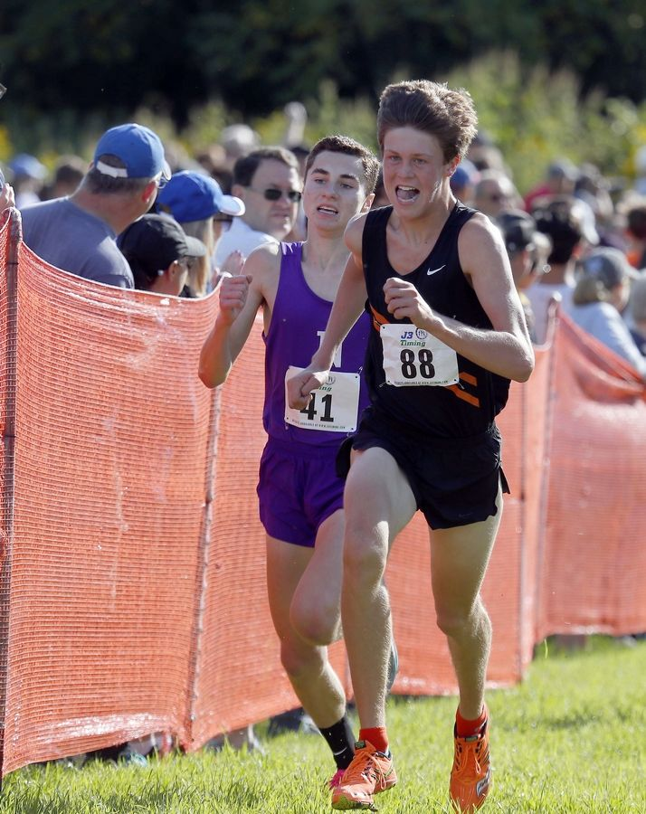 Luke Schildmeyer of St. Charles East, pictured racing against Downers Grove North's Evan Cummins, is part of a Saints team that heads to state Saturday ranked No. 1 in Class 3A.