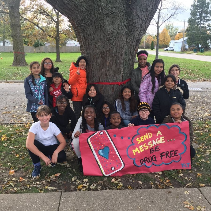 Beulah Park's Youth Leadership Team is sending a Message to Be Drug Free by putting red ribbons around treesKatrina Wiltse