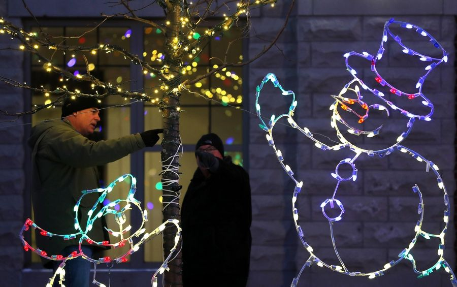 Rotary members Scott Amundsen, left, and Geoff Roehll make adjustments to a light display Tuesday night. The NaperLights holiday display is set up by volunteers from the Naperville Sunrise Rotary. The event moves this year from Naper Settlement to Water Street overlooking the DuPage River between Webster and Main streets.