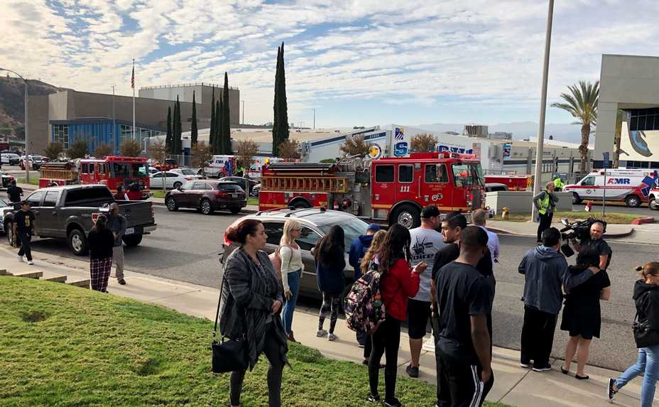 People wait for students and updates Thursday outside of Saugus High School after reports of a shooting in Santa Clarita, California.