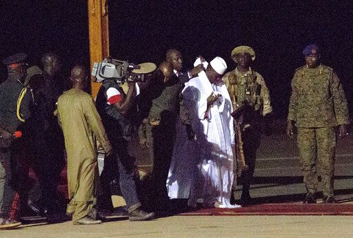 FILE - In this file photo dated Saturday Jan. 21, 2017, Gambia's defeated leader Yahya Jammeh, wearing white, departs at Banjul airport.  Gambia's longtime dictator Yahya Jammeh, who fled into exile three years ago after an election loss, says he wants to return home, according to an audio recording released by his political party Tuesday Jan. 14, 2020.