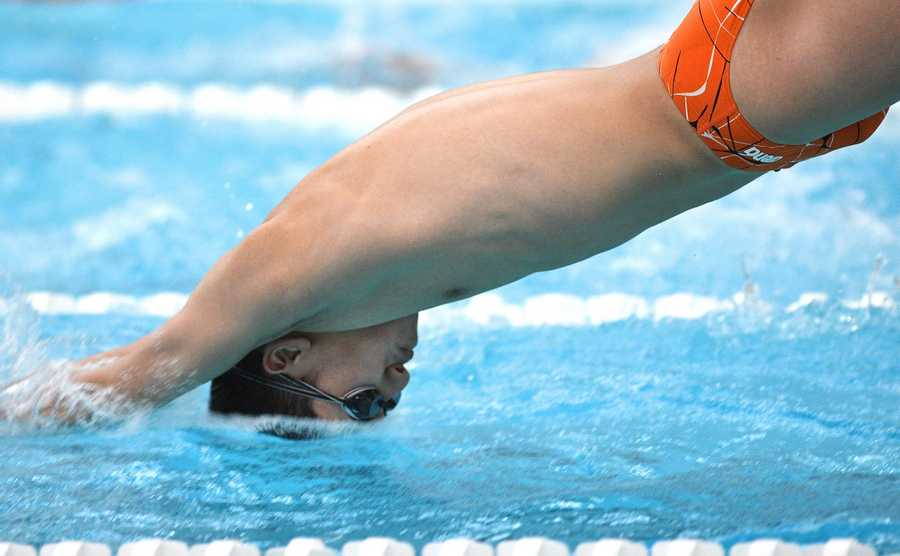 Libertyville's Andrew Yan hits the surface as he starts his leg of the 200-yard medley relay in a boys swimming and diving meet against Mundelein in Libertyville Thursday.