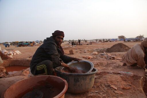 In this photo taken on Monday Jan. 22, 2020 a man pans for gold in Kidal, Mali. A gold rush is underway in northern Mali in an area where al-Qaida-linked militants operate, raising concerns that new profits from the artisanal mining could benefit not only the local economy but also the Islamic extremists. A coalition of armed Tuareg rebels known as the CMA controls the Kidal region and its leaders are the ones overseeing the gold panning activities.