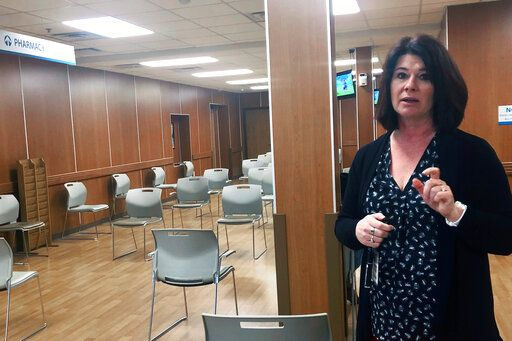 Heather Burton, president and CEO of Central Counties Health Centers, in Springfield, Ill., stands in an empty waiting room Thursday, March 26, 2020 and explains how federally established clinics like hers have lost up to 70% of their revenue from routine and preventive doctor's visits which they've canceled to slow the spread of the novel coronavirus. Hundreds of health care facilities in Illinois that largely serve low-income and minority communities are facing financial chaos because they've canceled most routine doctor visits in an attempt to stymie the coronavirus pandemic, according to an industry organization's report.