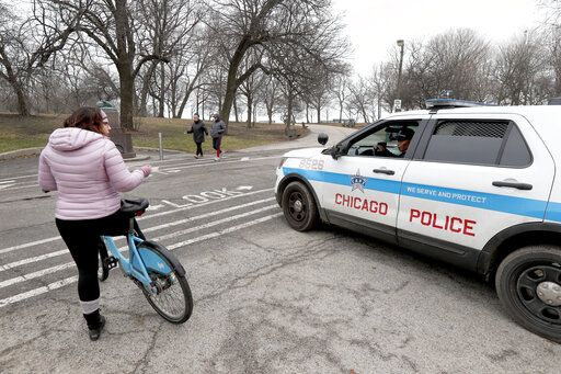 A Chicago police officer notifies a cyclist that the trails in Promontory Park, in the city's Hyde Park neighborhood along Lake Michigan, are closed in an effort to limit the spread of COVID-19 infections, Thursday, March 26, 2020, in Chicago. The new coronavirus causes mild or moderate symptoms for most people, but for some, especially older adults and people with existing health problems, it can cause more severe illness or death.