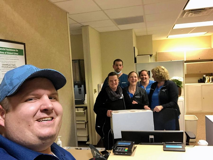 Kris Schoenberger, owner of the BBQ'd Productions restaurants, poses for a picture with emergency personnel at Northwestern Medicine Outpatient Center in Grayslake last Thursday after delivering meals donated by the community.