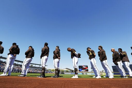 San Diego Padres players and coaches line up during playing of the national anthem before a spring training baseball game against the Los Angeles Dodgers, Monday, March 9, 2020, in Peoria, Ariz.