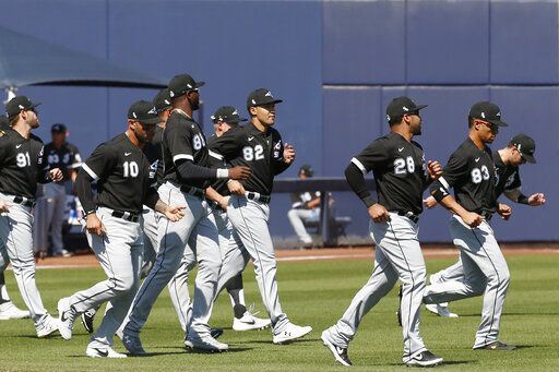 Chicago White Sox players warm up before a spring training baseball game against the Milwaukee Brewers, Wednesday, March 4, 2020, in Phoenix, Ariz.