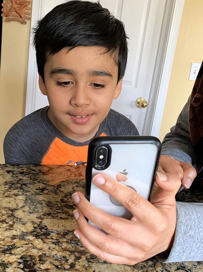 Maaz Khan, 8, of Bolingbrook, an autistic third-grader at Plainfield Unit District 202, chats with his teacher through FaceTime while schools are closed. Maaz's teachers and therapists stay in touch through email, sharing pictures and video chats.