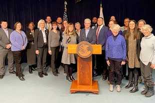 Representatives and senators supporting the Fair Maps Amendment legislation stand with CHANGE Illinois Executive Director Madeleine Doubek, center, at a press conference announcing the bills in February.