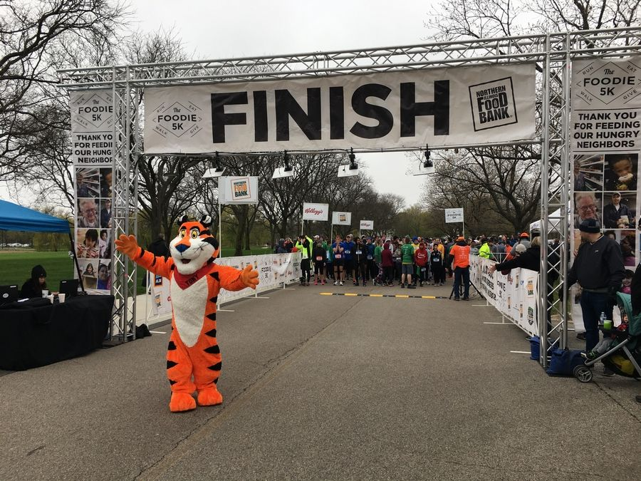 Tony the Tiger clears the finish line at the Foodie 5K sponsored by Kellogg's to benefit the Northern Illinois Food Bank in 2019. This year the annual Foodie 5K race on April 18, 2020 has been transformed into a virtual road race to raise funds at a critical time when food banks are stretched to the limit, and providing food to more people every day.