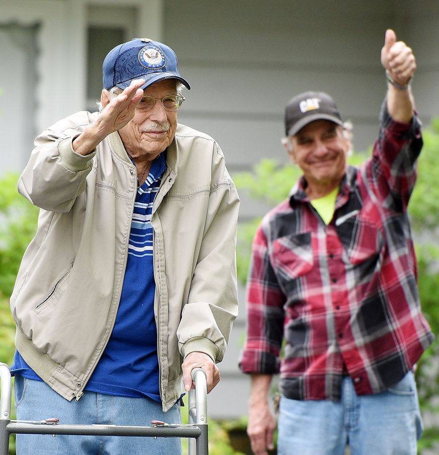 Bob Piper salutes and his son, Steve, gives a thumbs-up as friends and local veterans groups hold a drive-by parade celebrating Bob's 98th birthday Friday in Naperville. A World War II veteran, Bob Piper served in the U.S. Navy.