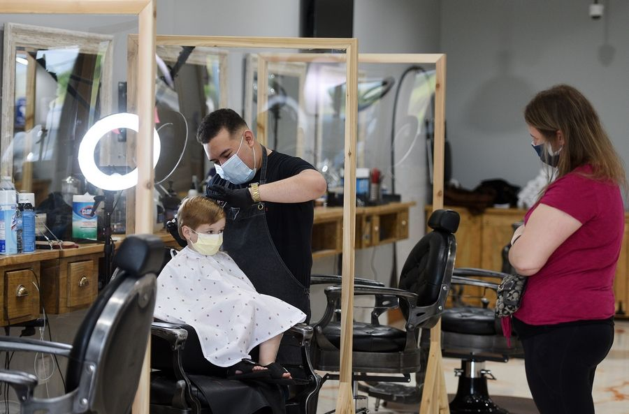 "Dawson Naleck, 3, of Pingree Grove gets his hair cut by stylist Alex Medina as his mom Julie looks on at Sauvage Barber Parlor in Elgin Friday. ""He definitely needed this haircut,"" Julie Naleck said of her son. ""He hasn't had one since February."" It was Medina's second client of the day already at 9:15 a.m. ""Feels great to be back at work,"" he said. ""The masks have been a little weird when cutting around the ears at first but you get used to it."""