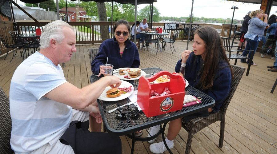 "Joe Fye and his wife Jeanette and daughter Sammie, 21, of Hawthorn Woods enjoy a meal on the outdoor patio at Docks Bar and Grill on Bangs Lake in Wauconda on Friday. Joe described the outing as ""freedom"" as his daughter chimed in, ""I'm just glad to be out."" His wife called several places last night to track down someone that would be open today as the ban on restaurants lifted because of the coronavirus pandemic had decreased."