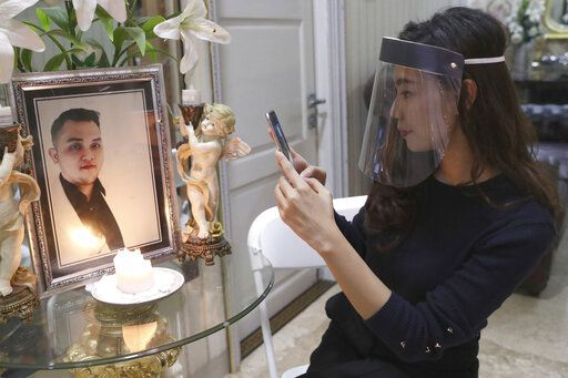 Tri Novia Septiani takes a photo of a portrait of her fiance Dr. Michael Robert Marampe during an online memorial service to mark the 40th day since Marampe passed away due to COVID-19 in Jakarta, Indonesia, on June 5, 2020. Marampe knew what he wanted to be since he was a kid: a doctor and a pianist. He became both, and his passion for music even led him to Septiani - a woman he never got to marry because he got the coronavirus. Marampe became one of dozens of doctors the coronavirus has claimed so far in Indonesia.