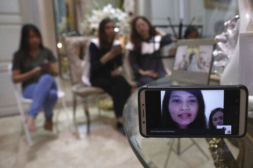 A relative of Dr. Michael Robert Marampe is seen through a mobile phone screen as she attends an online memorial service to mark the 40th day since Marampe passed away due to COVID-19 in Jakarta, Indonesia, on June 5, 2020. Marampe knew what he wanted to be since he was a kid: a doctor and a pianist. He became both, and his passion for music even led him to Tri Novia Septiani - a woman he never got to marry because he got the coronavirus. Marampe became one of dozens of doctors the coronavirus has claimed so far in Indonesia.
