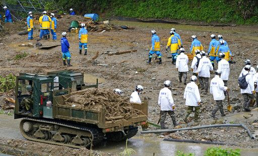 Police officers continue a search operation for missing persons at the site of a mudslide in Tsunagi town, Kumamoto prefecture, southwestern Japan, Tuesday, July 7, 2020. Floodwaters flowed down streets in southwestern Japanese towns hit by deadly rains that were expanding across the region Tuesday. (Koji Harada/Kyodo News via AP)
