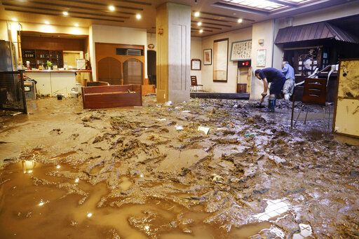 The lobby of a hot-spring hotel is covered with mud after flooding caused by heavy rain in Hita city, Oita prefecture, southwestern Japan, Tuesday, July 7, 2020. Floodwaters flowed down streets in southwestern Japanese towns hit by deadly rains that were expanding across the region Tuesday. (Miyuki Saito/Kyodo News via AP)