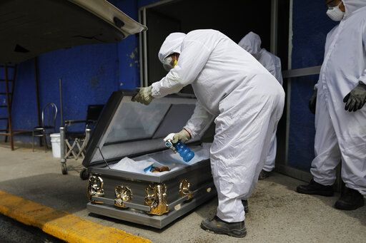 A worker wearing protective gear sprays disinfectant solution inside the coffin of a person who died from suspected COVID-19, as the body arrives at the crematorium at Xilotepec Cemetery in Xochimilco, Mexico City, Monday, July 27, 2020.