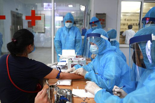 A health worker draws blood for COVID-19 test in Hanoi, Vietnam on Friday, July 31, 2020. Vietnamese state media on Friday reported the country's first-ever death of a person with the coronavirus as it struggles with a renewed outbreak after 99 days without any cases.